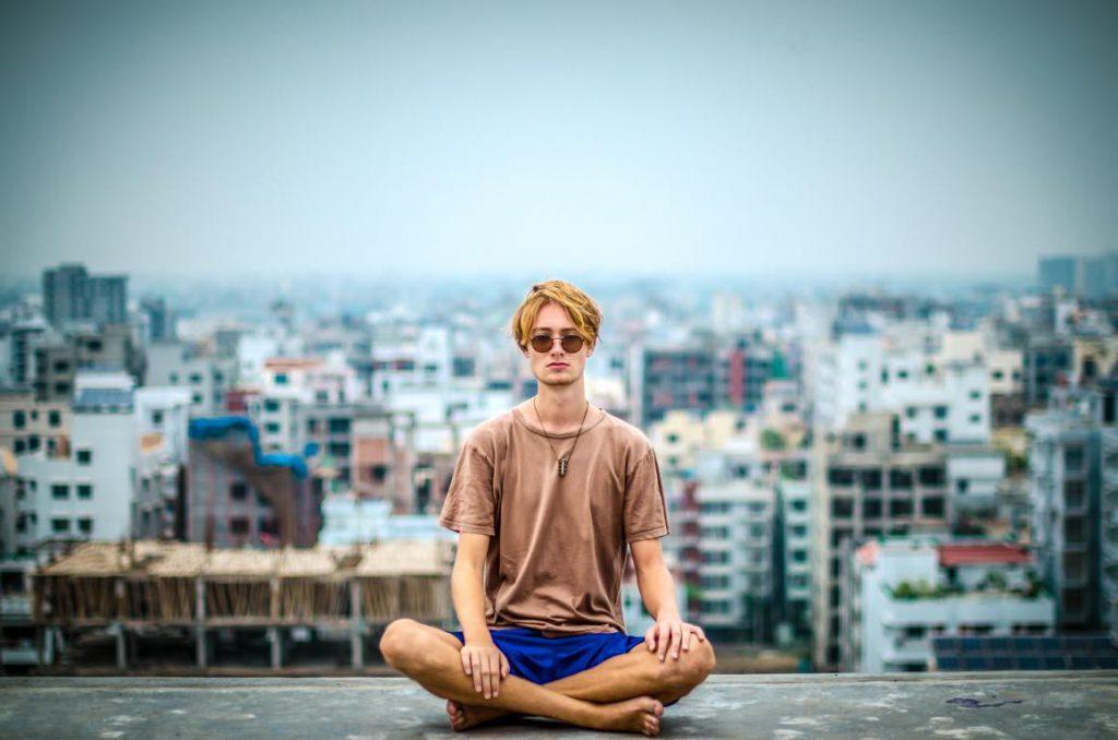 Mann-vor-Häuser-Kulisse-meditiert