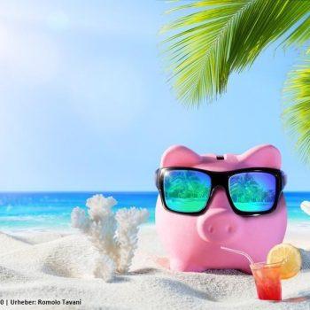Rosa Sparschwein mit Sonnenbrille am Strand